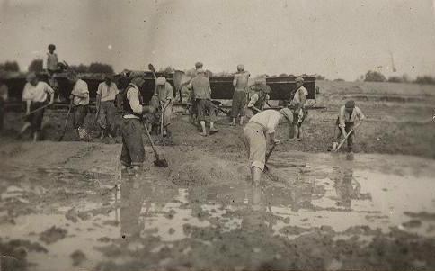 Żydzi pracujący na boso przy wybieraniu ziemi na polach Pólko – Norzyce i ładowaniu jej do wagoników, które następnie pchali ręcznie na usypywany wał rzeczny.